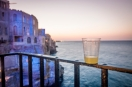 My FAVOURITE writing spot. My hotel and the small balcony jutting out from a cliff face, overhanding the Adriatic Sea. Glass of Limoncello for inspiration! Polignano a Mare, Bari, Italy.